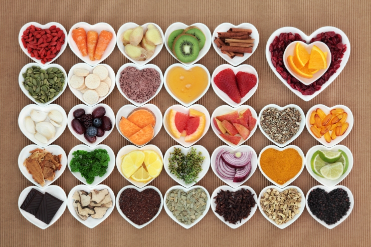Health food for flu and cold remedy cures high in antioxidants and vitamin c with tablets, medicinal herbs and spices in heart shaped dishes.